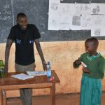 The Water Project: Friends School Mutaho Primary -  Student Demonstrates Toothbrushing With Help Of Trainer Protus