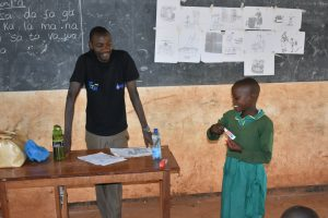 The Water Project:  Student Demonstrates Toothbrushing With Help Of Trainer Protus