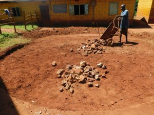 The Water Project:  Laying The Stone Rain Tank Foundation