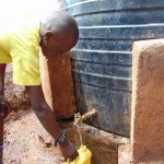 The Water Project: Gamalenga Primary School -  Student Drawing Water From The Tank