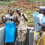 The Water Project: Bumavi Community, Joseph Njajula Spring -  Team Leader Catherine Chepkemoi And A Community Member Give Thumbs Up For Clean Water