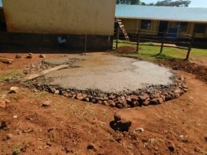 The Water Project:  Pouring Concrete Over Stone Foundation