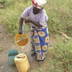 The Water Project: Nzimba Community -  Collecting Water From Unprotected Well