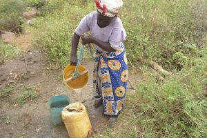 The Water Project:  Collecting Water From Unprotected Well