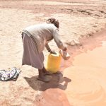 The Water Project: Nzimba Community A -  Pouring Water From Scoop Hole Into Container