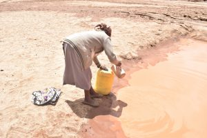 The Water Project:  Pouring Water From Scoop Hole Into Container