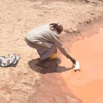 The Water Project: Nzimba Community -  Scooping Water
