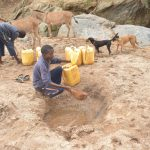 The Water Project: Mbitini Community A -  Collecting Water From The Scoop Hole