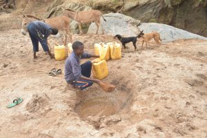 The Water Project:  Collecting Water From The Scoop Hole