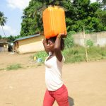 The Water Project: Lungi, Mahera, Mahera Health Clinic -  Child Carrying Water