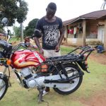 The Water Project: Lungi, Mahera, Mahera Health Clinic -  Young Man Working On His Motorbike