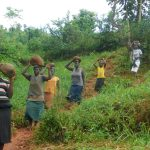 The Water Project: Emulembo Community, Gideon Spring -  Community Members Bringing Stones