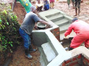 The Water Project:  Cement And Plaster Work As Children Look On