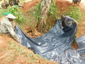 The Water Project:  Adding Plastic Tarp Over Backfilled Stones