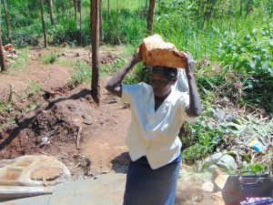 The Water Project:  Community Member Delivers Stone To Spring Site