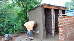 The Water Project:  Cementing Latrine Wall