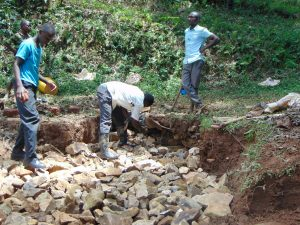 The Water Project:  Backfilling With Stones Begins