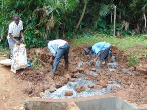 The Water Project:  Covering Tarp With Soil