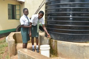 The Water Project:  Students Collect Water From A Small Plastic Tank
