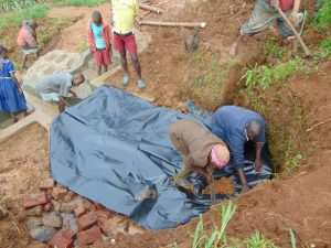 The Water Project:  Covering Stone Backfill With Thick Plastic Tarp