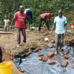 The Water Project: Bumira Community, Madegwa Spring -  Adding Plastic Tarp Over Backfilled Stones