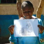 The Water Project: Banja Primary School -  Student Holds Training Materials