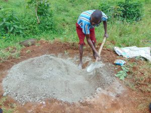 The Water Project:  A Boy Helps Mix Cement