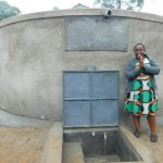 The Water Project: Shichinji Primary School -  Sanitation Teacher Madam Ellah Stands With Completed Tank