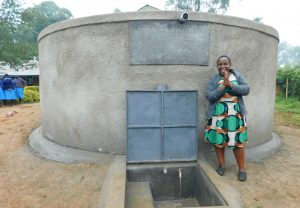 The Water Project:  Sanitation Teacher Madam Ellah Stands With Completed Tank