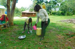 The Water Project:  Trainer Laura Pouring Water For Hanwashing Demonstration With A Child