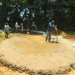The Water Project: Kapkures Primary School -  Adding Concrete To Rain Tank Foundation