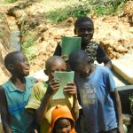 The Water Project: Bumira Community, Madegwa Spring -  Kids Pose With Training Materials At The Spring