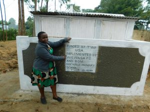 The Water Project:  Sanitation Teacher Madam Ellah Poses With The Girls Latrines