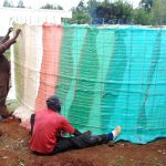 The Water Project: Ebulonga Mixed Secondary School -  Tying The Plastic Tarps Into Place