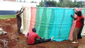 The Water Project:  Tying The Plastic Tarps Into Place