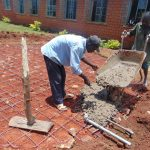 The Water Project: Demesi Primary School -  Adding Concrete Over Stones And Wire
