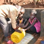 The Water Project: Emulembo Community, Gideon Spring -  Rinsing Container Before Using It
