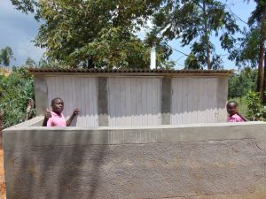 The Water Project:  Thumbs Up From Behind Boys Latrine Wall