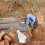 The Water Project: Emulembo Community, Gideon Spring -  Brick Laying Over Spring Foundation