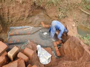 The Water Project:  Brick Laying Over Spring Foundation