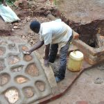 The Water Project: Masuveni Community, Masuveni Spring -  Cementing The Rub Wall