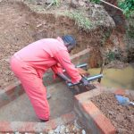 The Water Project: Munenga Community, Francis Were Spring -  Pipe Setting
