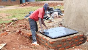 The Water Project:  Fitting The Manhole Cover To The Access Point