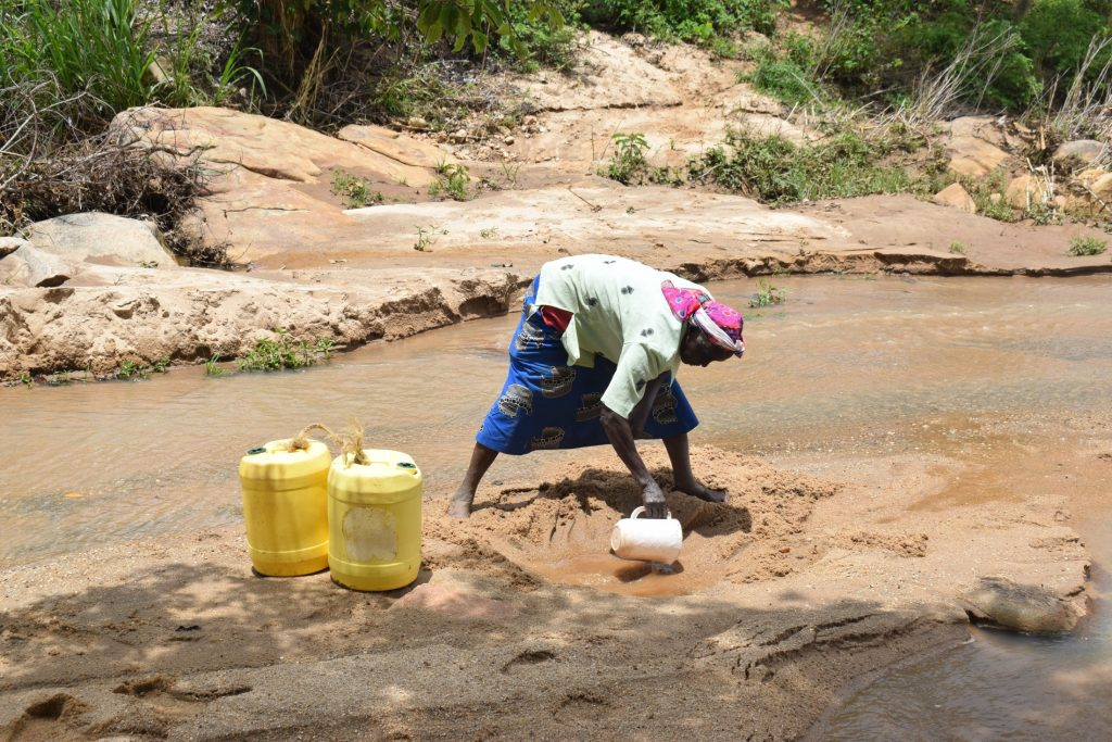 The Water Project : kenya20316-20317-scooping-water-2