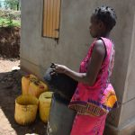 The Water Project: Nduumoni Community A -  Filling Up Water Storage Container