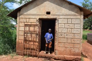 The Water Project:  Boy Stands In Front Of Latrine Block