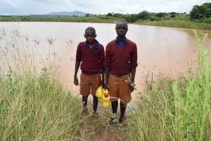 The Water Project:  Students Stand In Front Of Open Water Source