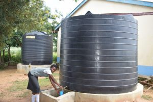 The Water Project:  Student Fetching Water From Small Tank