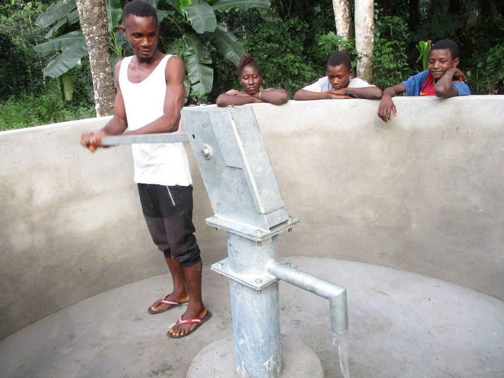 The Water Project : sierraleone18258-community-member-pumps-the-well