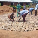The Water Project: Mukama Primary School -  Tying Wire On Top Of Rain Tank Stone Foundation